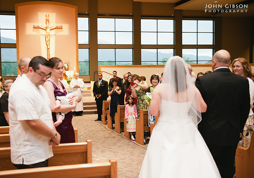 The groom sees his bride as she walks down the aisle