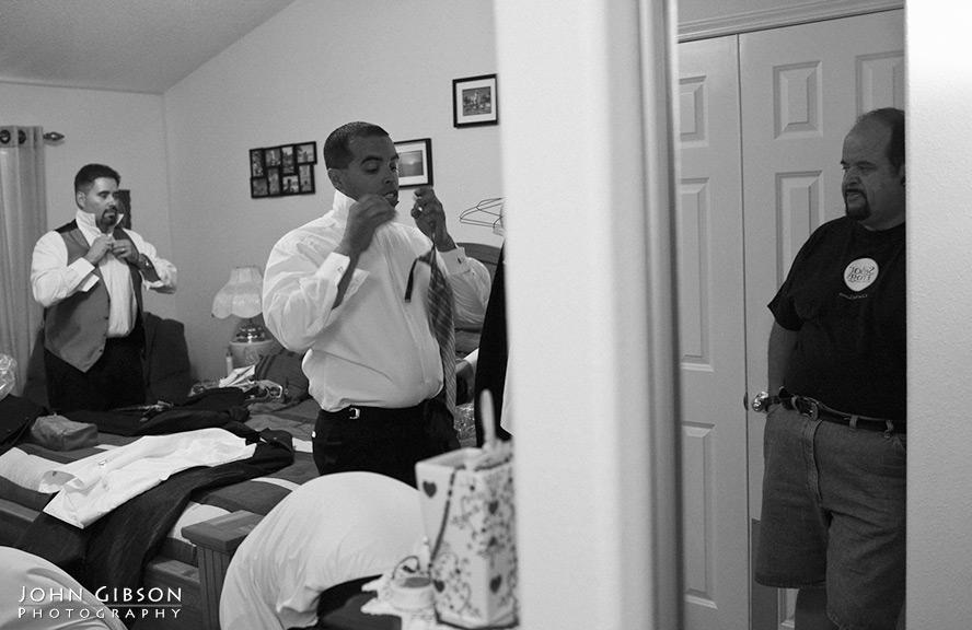 Juan's dad looks on as he fastens his tie