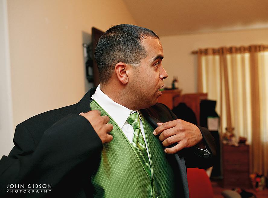 The groom pulls on his jacket