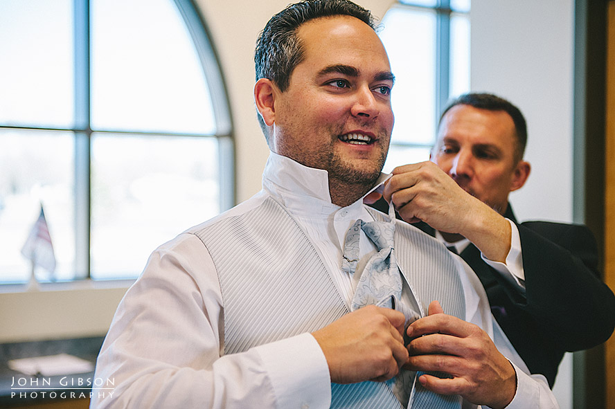Best man assists the groom with his tie